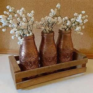 Set of distressed glass bottles with wood crate